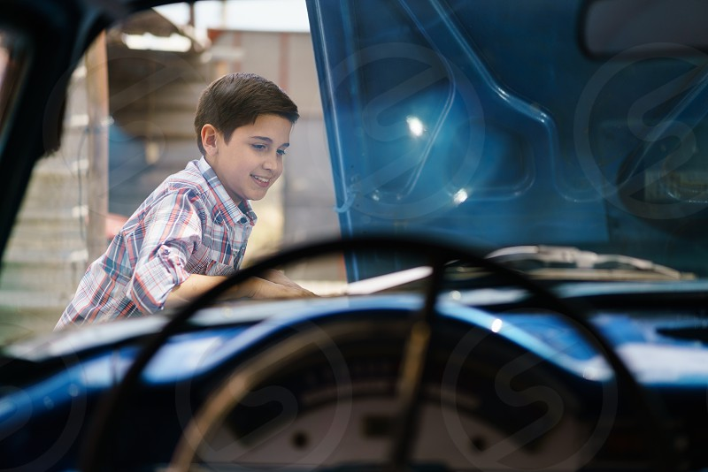 kid car boy child auto curiosity engine passion repair broken people learning active adjust admiring admiration amazed amazement american automobile examining expression fixing grandchild grandson happy hispanic hood latin american learn looking motor old one person smile smiling steering wheel transportation vehicle vintage yard young youth photo
