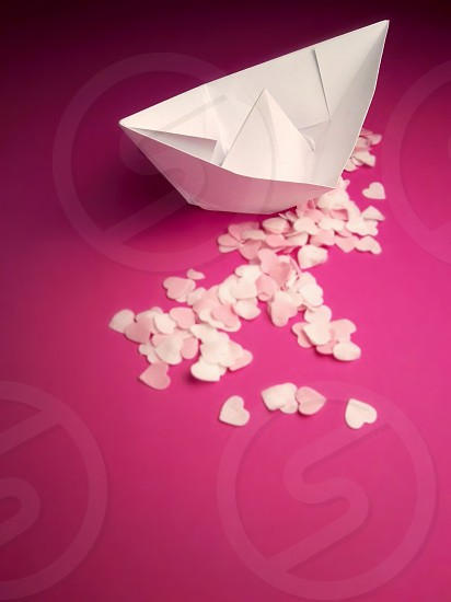 white single paper boat on pink background photo
