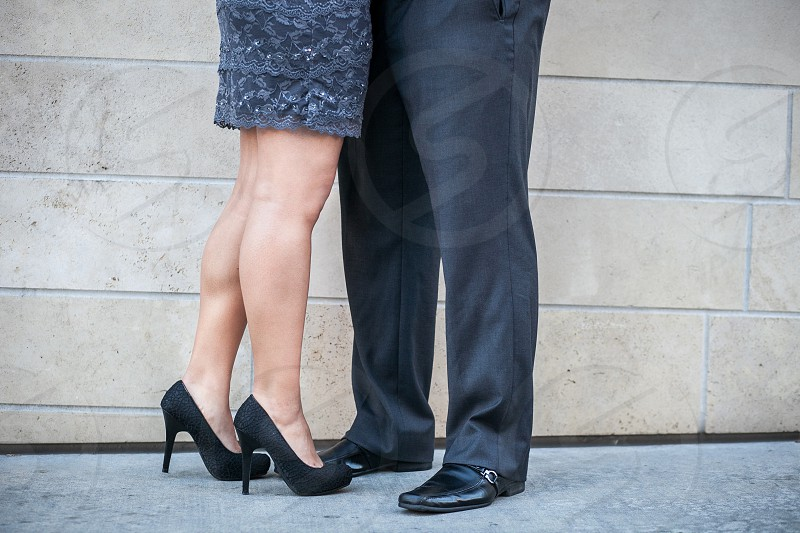 The feet of a sharply dressed couple.  Grey wall  stone cement sidewalk dressy slacks high heels stilettos casual formal lace embrace love hug legs feet calves.   photo