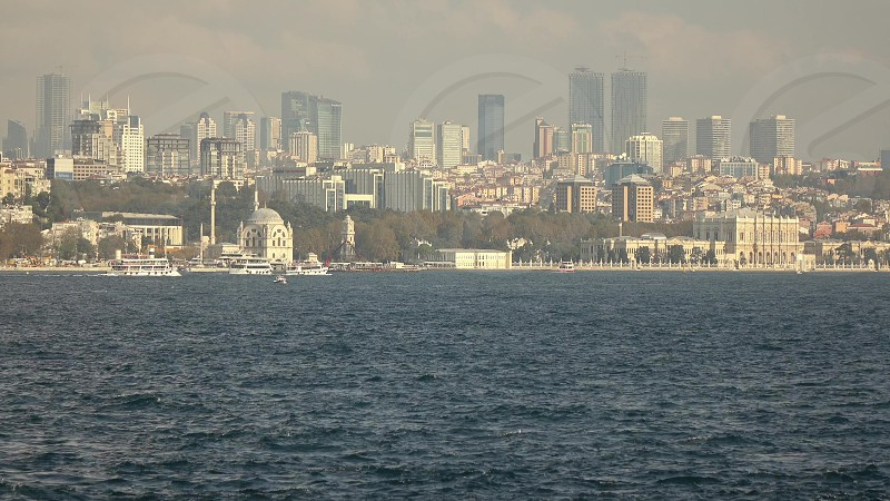 Turkish bank of Bosphorus strait with modern buildings and skyscrapers and moving tourisyic ships Istanbul Turkey in summer sunny day. Video in 4K UHD 3840 2160p. photo