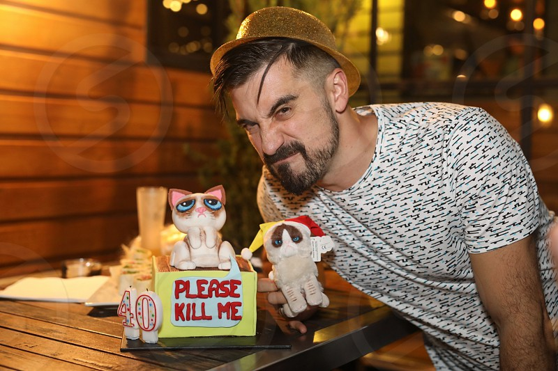 Person posing next to a Grumpy Cat birthday cake photo