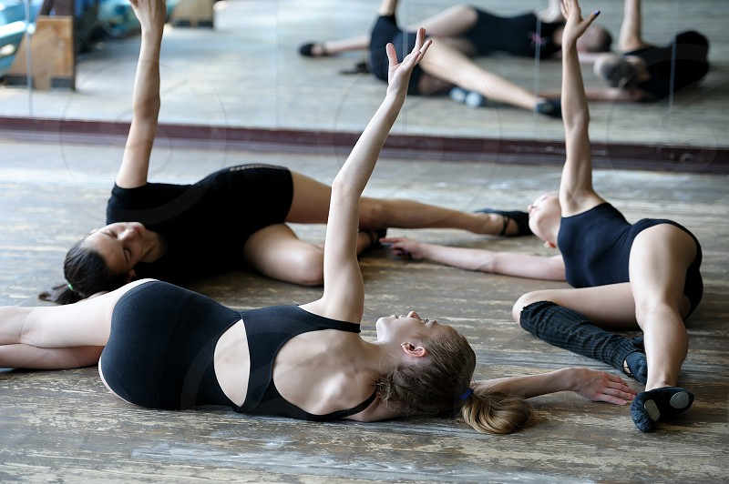 Three young ballet dancers on the floor rehearsing position in the ballet photo