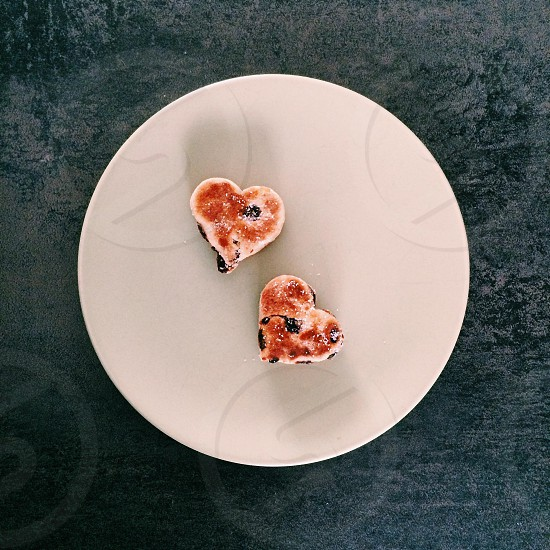A pair of delicious homemade heart-shaped Welsh cakes on a round plate photo