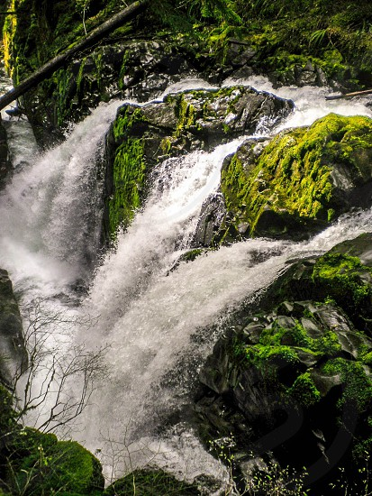 time lapse of waterfall  surrounded by green mosses photo