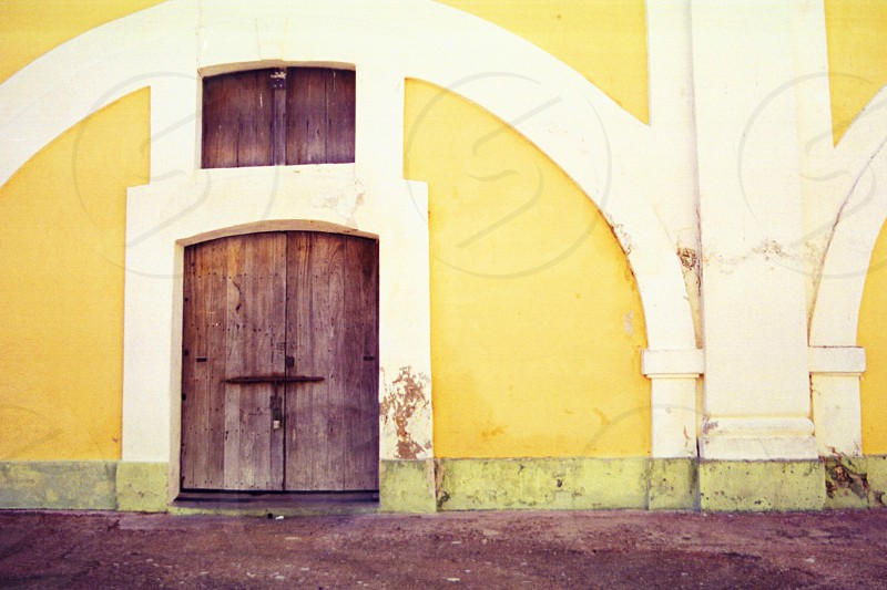 yellow building white arches wooden door photo