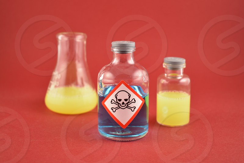 Vial of poison. Vial with warning pictogram. Laboratory accessories. Chemical glass on a red background. Chemical glass containers with liquid photo
