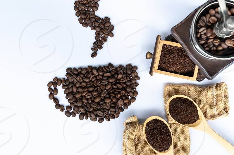 coffee beans in coffee cup shaped with wooden grinder and sack photo