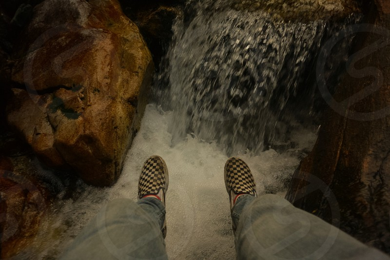 checkerboard vans hanging over a waterfall photo