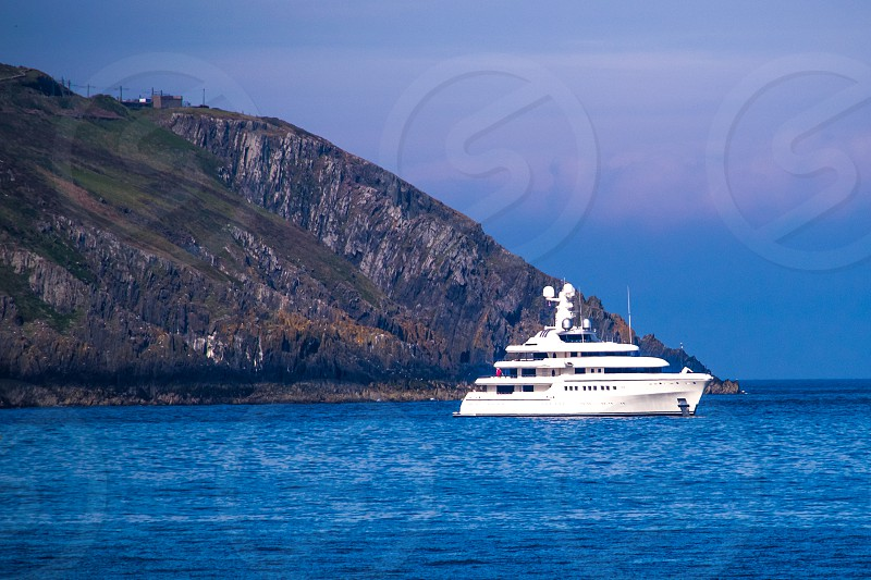 white cruise ship on body of water with view of mountain photo