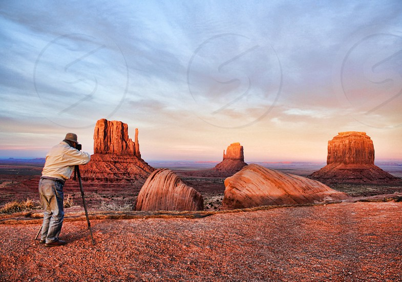 A photographer is seen from behind as he photographs the beautiful red rock formations of Monument Valley Arizona. photo