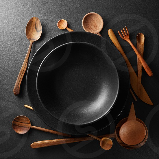 black plates and wooden spoon fork knife on a black table. photo