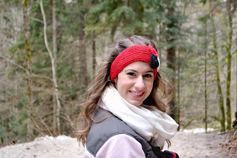 smiling woman wearing grey and white coat white scarf and red headband near tall trees during daytime photo