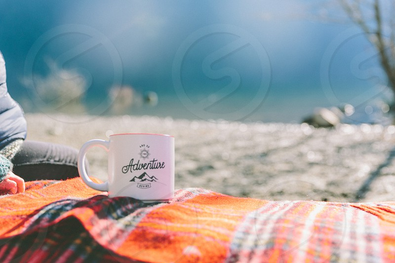 A cup with the words 'adventure' written on it sitting on a log.  photo