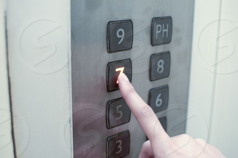 A young female is pressing the button number seven of an elevator photo