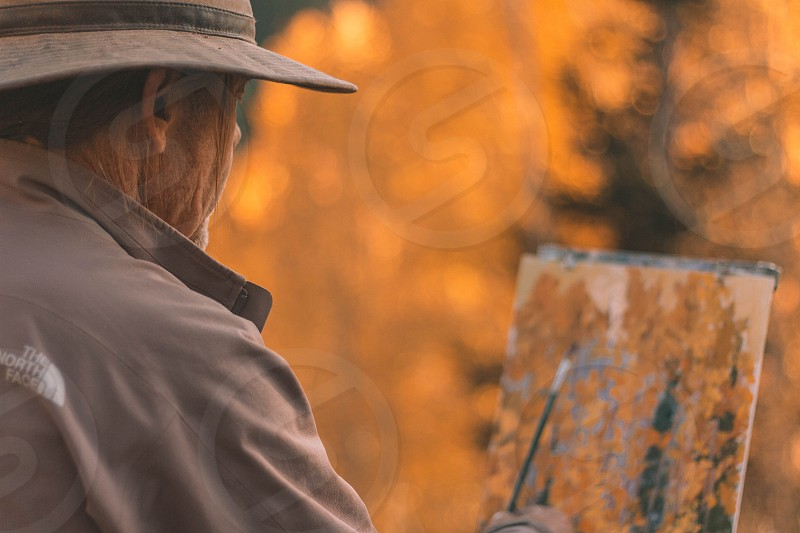 man wearing a brown hat and brown jacket painting yellow autumn trees photo