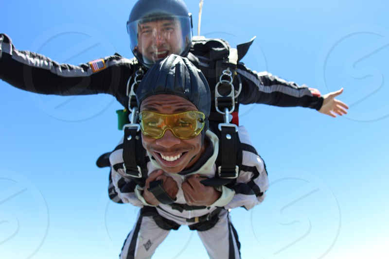 2 men tandem skyjumping in clear blue sky photo
