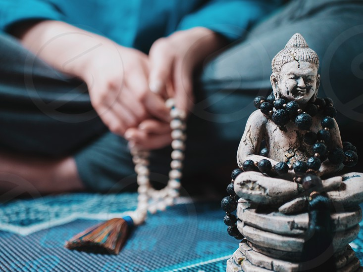 Concentrated woman praying with wooden rosary mala beads. Namaste. Close up statue of Buddha. photo