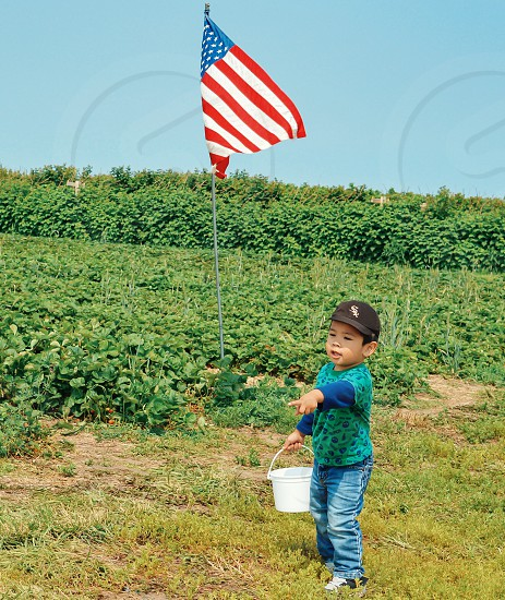 boy holding white plastic bucket wearing blue jeans and black fitted cap near to u.s.a flag standing on green grass field during daytime photo
