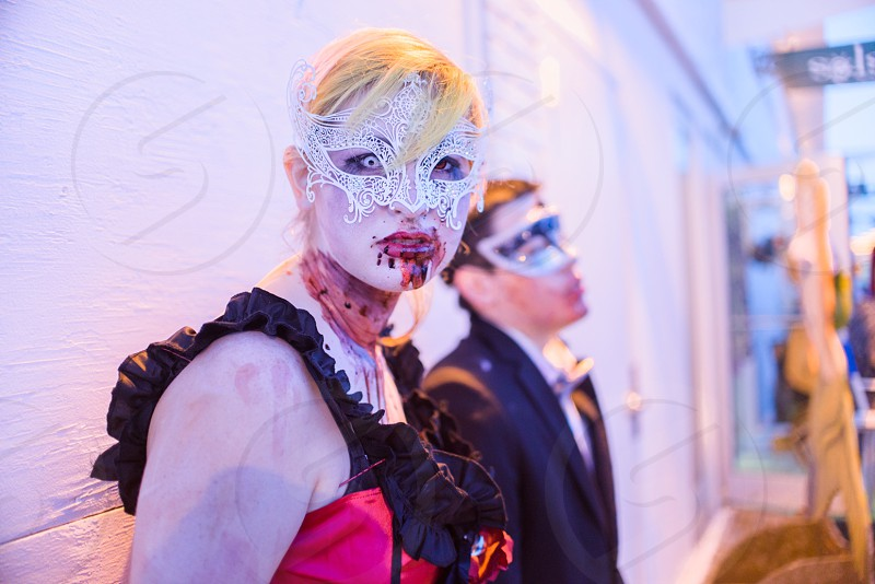 woman in pink and black sleeveless dress and man in black suit jacket in zombie costumes photo