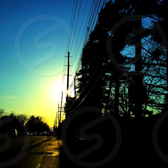 Dusk sunset light trees powerlines cars roads sunlight silhouette driving photo