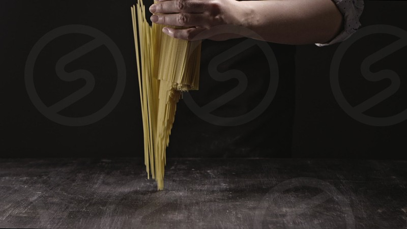 Falling vertical italian pasta from woman's hand on a wooden kitchen table. Slow motion Full HD video 240fps 1080p. Concept of italian food and cooking dinner. photo