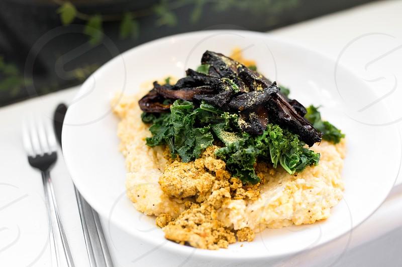 "Vegan grits bowl with tofu scramble kale and portobello ""bacon."" photo"