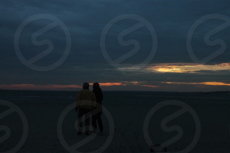 2 person standing on white sand photo
