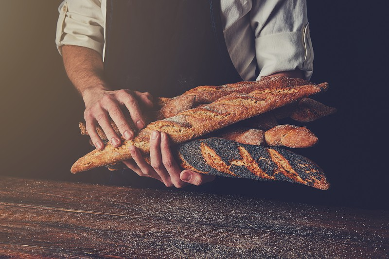 Freshly baked baguettes hold a man's hands against a background of a wooden table tonned photo photo