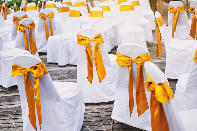 The random white spandex chairs cover with gold color organza sash decoration waiting for beach wedding venue arrangement. Beach wedding preparation. photo