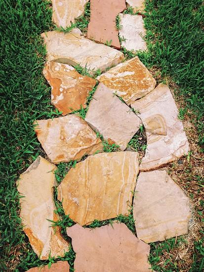brown stones flooring on grass field photo