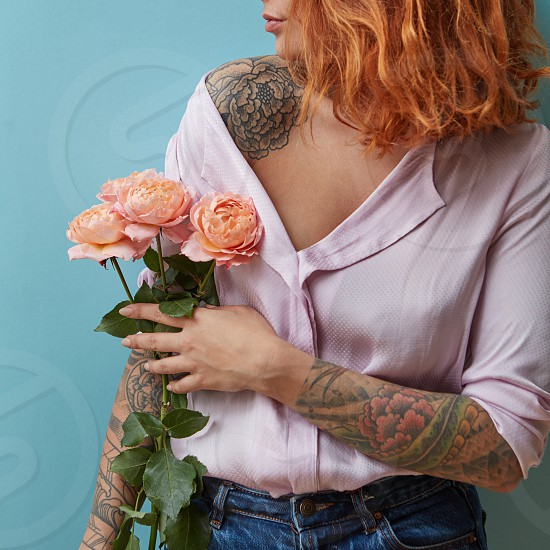 A girl with a tattoo on her hand holds delicate pink roses around a blue background with space for text. Valentine's Day Gift photo
