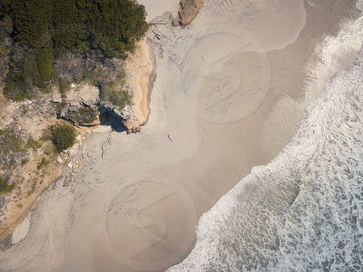 Aerial drone view at a beach section of Riviera Nayarit Mexico with a woman lying on her back tanning. photo