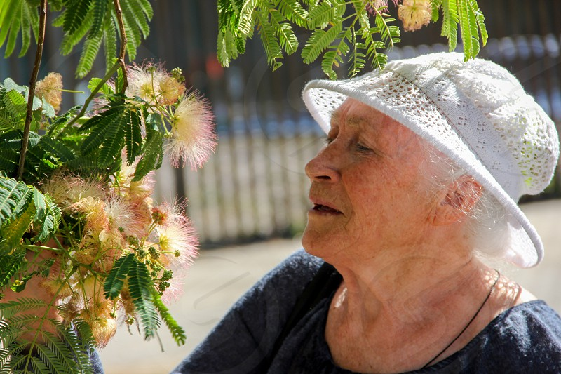 Portrait of a cute elderly lady in a knitted sun hat with flowers photo