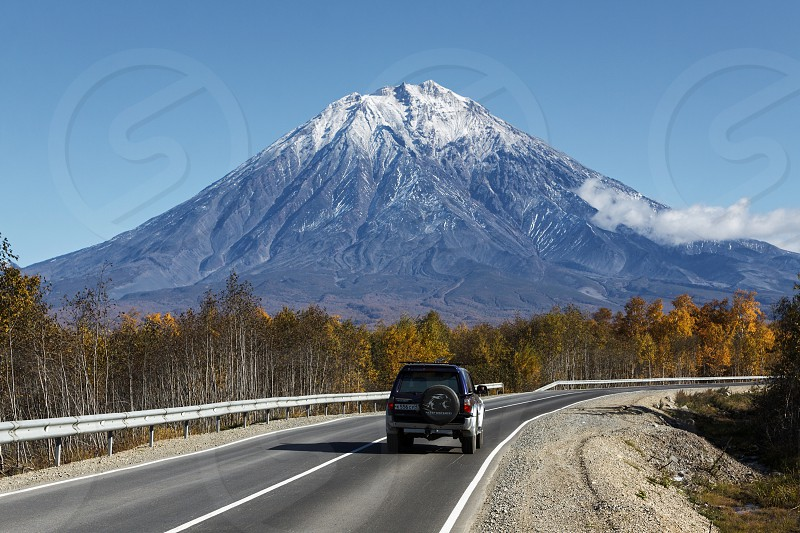KAMCHATKA RUSSIA - SEPTEMBER 30 2012: Autumn view of the car goes on the road to the active Koryaksky Volcano on Kamchatka Peninsula on a sunny cloudless day with blue skies. Russia Far East. photo