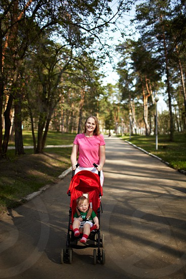 Young smiling mother with her 1 year son in the buggy walking outdoors in the park. Springday natural colors shallow dof (prime 35mm L optics) photo