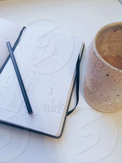 Sketchbook (Klein notebook) with grid line paper and a ceramic mug of coffee. The mug is hand-thrown painted and glazed. The notebook is being used to sketch UI elements for a website with a pencil.  photo