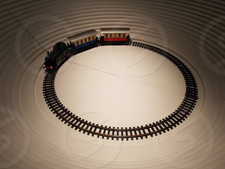 A toy train rides in a circle in the center of a small stadium. photo