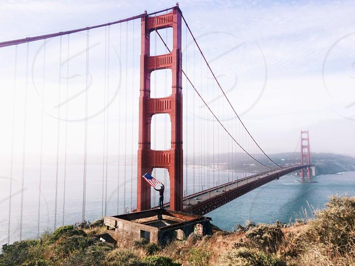 person waving american flag near golden gate bridge photo
