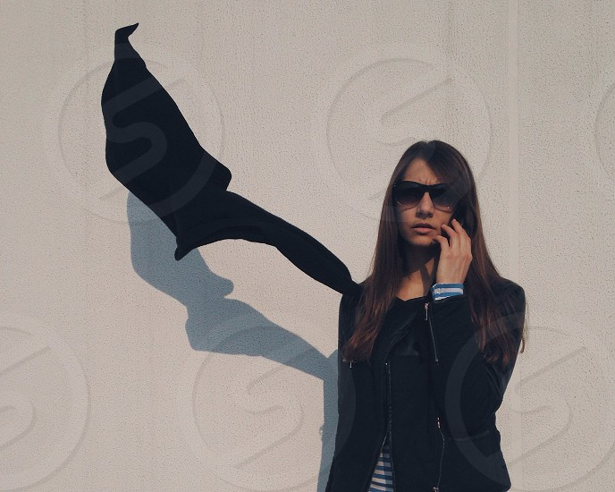 woman with brown long hair in black jacket standing near white wall photo