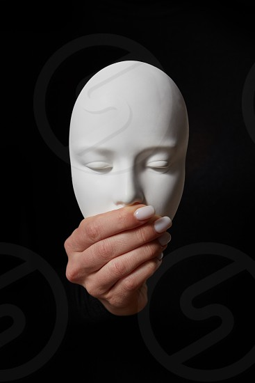 Woman fingers close mouth of gypsum mask face on a black background copy space. Speak no evil. Concept three wise monkeys photo