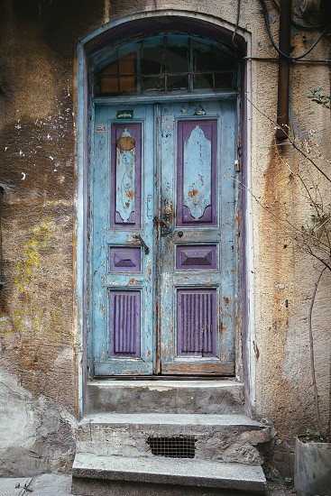 closed blue and purple wooden door of brown concrete building with damaged concrete stairs photo