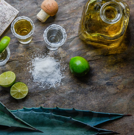 half sliced lime near salt with salted rim tequila shots beside decanter photo