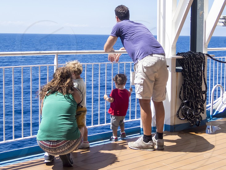 family watching the sea from the deck of a ship photo