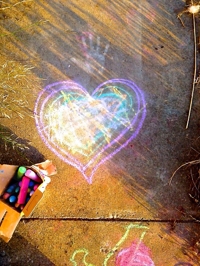grey sidewalk with pink and green chalk heart drawing photo