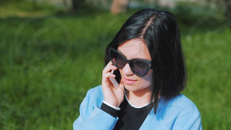 Close-up portrait of young beautiful businesswoman looking at camera with smile outdoors professional female manager wearing glasses and suit slow motion. Student girl autumn street photo
