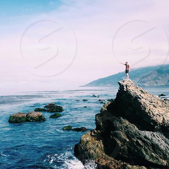 man standing on rock near beach photo