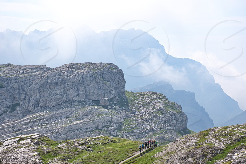 Group of mature and senior hikers hiking in Brenta Dolomites. Scenic rocky landscape photo