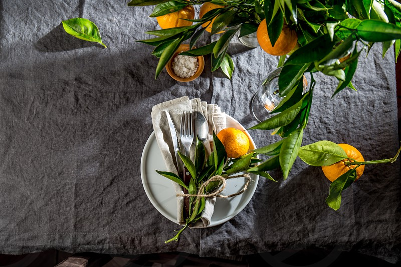 Table setting with white plate cutlery linen napkin and orange tree branch decoration on gray linen tablecloth . Close up. Table with table setting and shair. photo