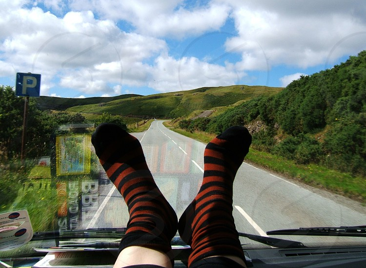 campervan country road hills windscreen road map reflection stripy socks photo