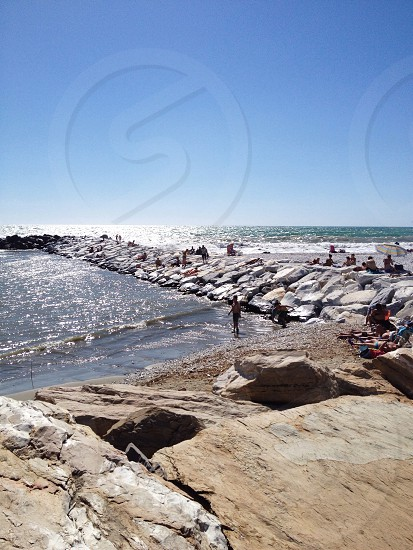 people standing and sitting near breakwater during daytime photo